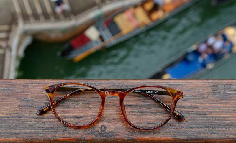 briller som ligger på en bro med båter under