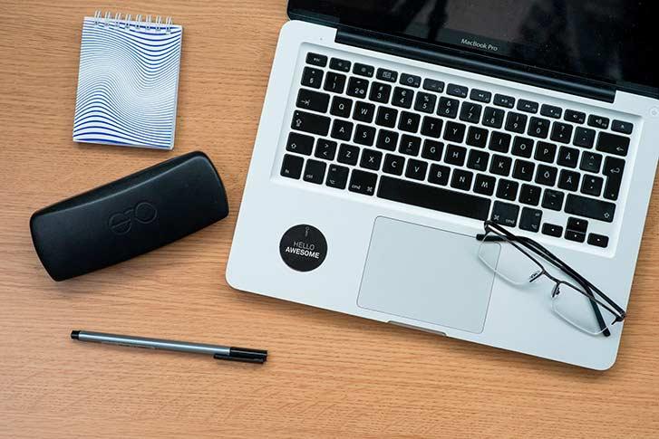 briller, en penn, et brilleetui og en PC på en benk