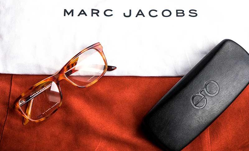 briller fra marc jacobs og et billeetui fra extra optical på et bord