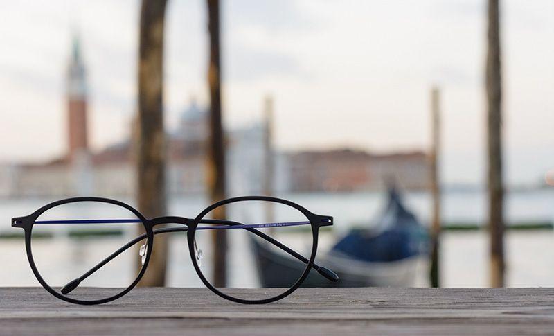 briller som ligger på et bord med hav i baggrunden
