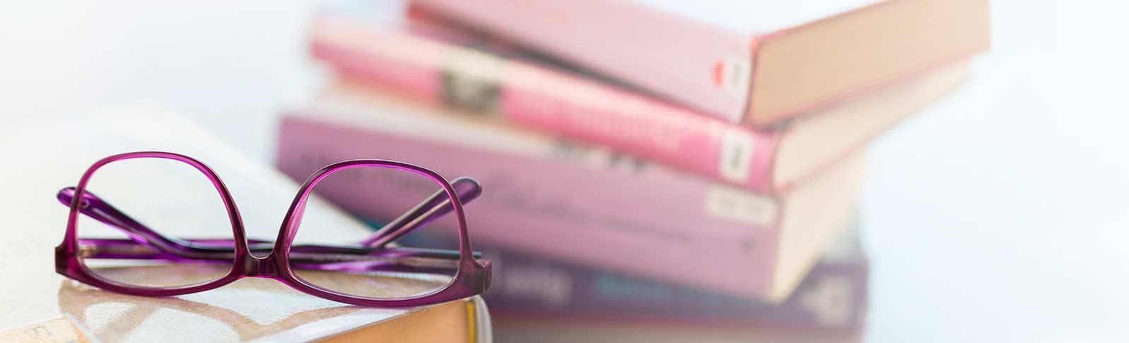 bøker og briller på et bord