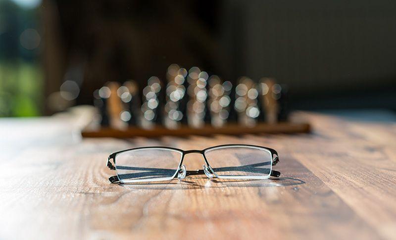 briller på et bord med et sjakkbrett i bakgrunnen